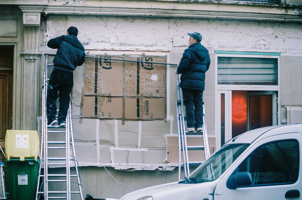 Two Men on Ladders Working on a Property's Exterior