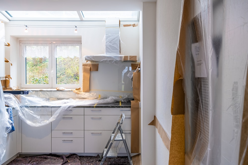 A Kitchen with Marble Countertops and White Furniture Undergoing Renovation