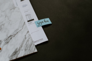 Property paperwork with a signature post-it